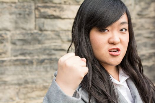 Portrait of young aggressive woman in front of a stone wall looking angry and holding fist