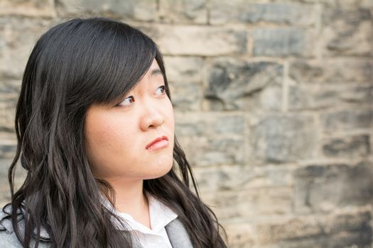 Portrait of young girl in front of a stone wall looking upset and looking away