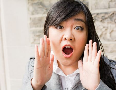 Portrait of attractive young woman looking surprised and screaming out loud