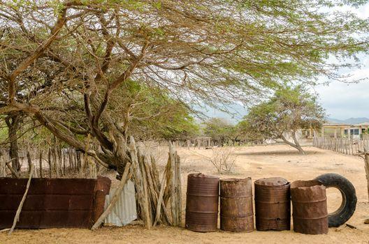 Rusted barrels making a fence in a rural village in La Guajira, Colombia