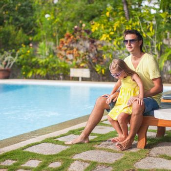 Little girl with her father have fun near the swimming pool at exotic resort