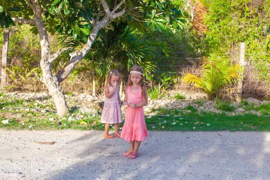 Two little girls on footpath in a tropical country