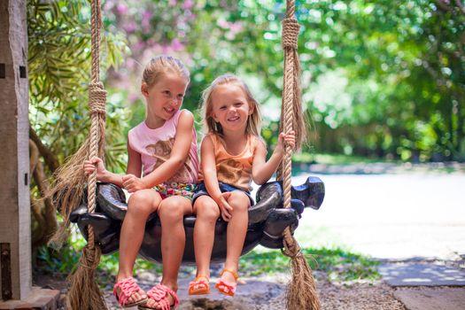 Little girls swinging in a cozy lovely flowered courtyard