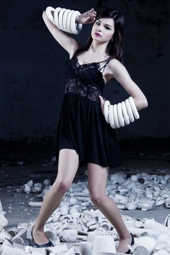 Fashion photoshoot with  a beautifulyoung woman holding pieces of porcelain