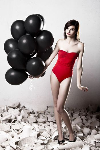 Fashion photoshoot with  a beautiful young woman holding balloons