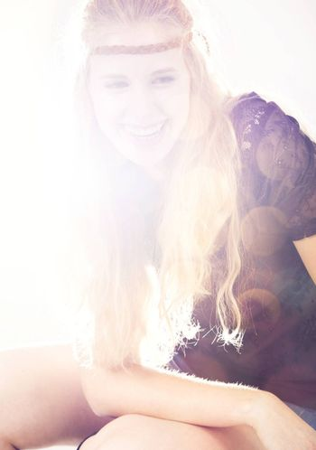 Beautiful fashion woman smiling and posing with light come from the beackground