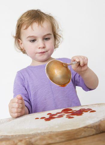 child putting sieved tomatoes on dough. studio shot in grey background