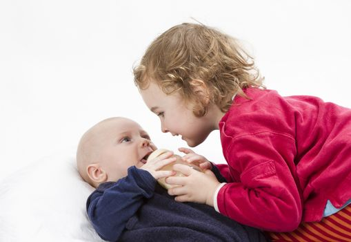 cute girl playing with her baby brother in light grey background. Studio shot