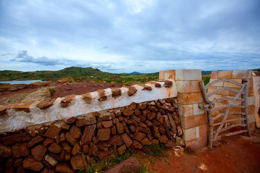 Masonry red stonewall in Menorca with fence door