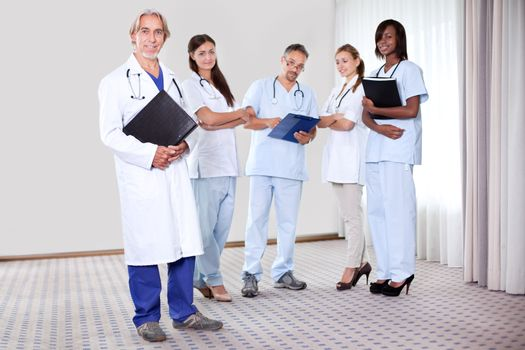 Team of professionals lead by mature doctor