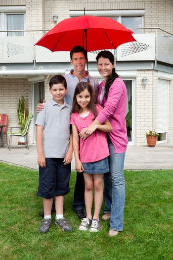 Happy family under one umbrella outside their home