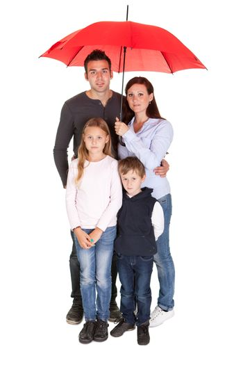 Happy young family standing under one umbrella