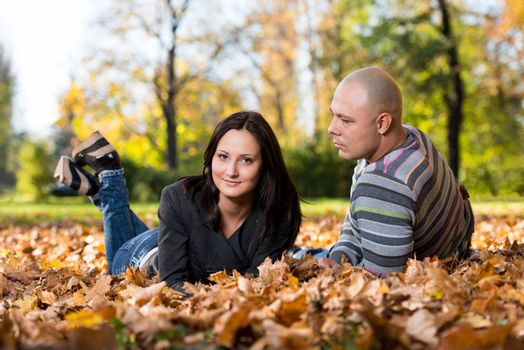 Happy Couple Sitting Together In The Woods During Autumn