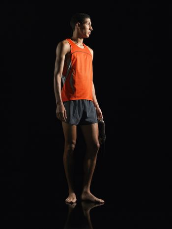 Athlete standing holding shoes