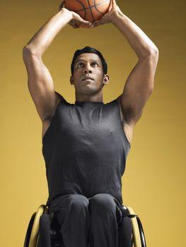 Paraplegic athlete sitting in wheelchair shooting basketball
