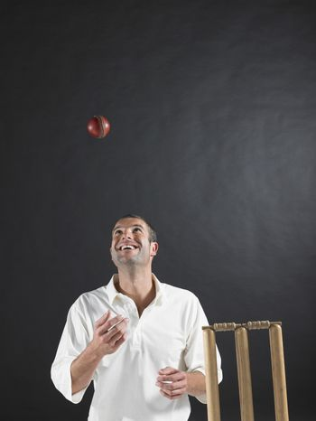 Happy young cricket player tossing ball in the air by stumps against black background