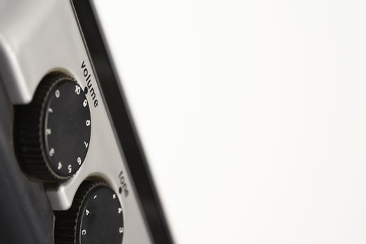 Closeup of volume and tone dials over white background