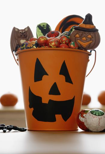 Bucket with Jack O'lantern face filled with sweets