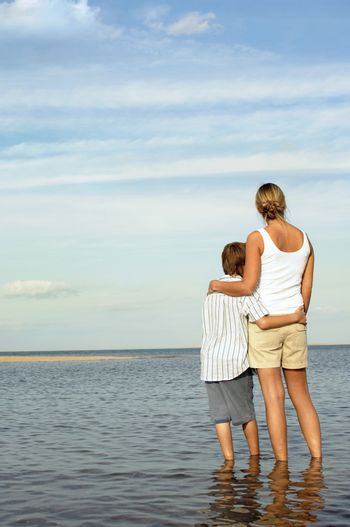 Rear view of mother and son enjoying the sea view