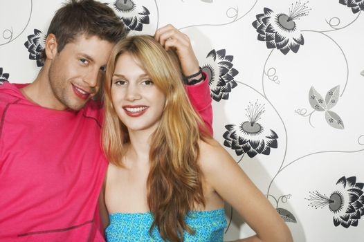 Portrait of a happy young couple against floral print wall