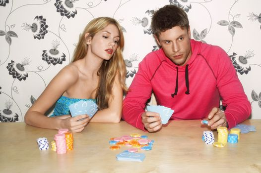 Couple playing cards as woman looks at man's cards