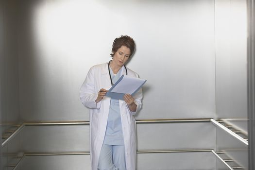 Female physician reviewing notes in the elevator