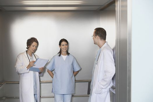 Male and female physicians talking in elevator talking