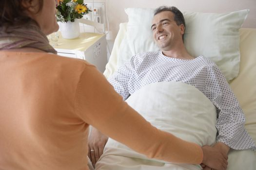 Rear view of a woman visiting man in hospital
