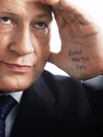 Closeup of a bored businessman with note on his palm