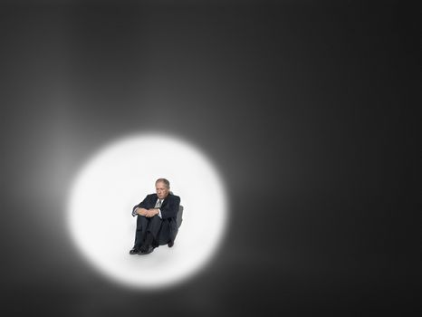 Middle aged businessman sitting in spotlight