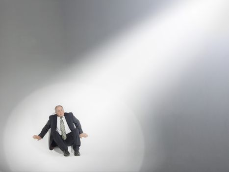 Businessman sitting and looking up at source of spotlight