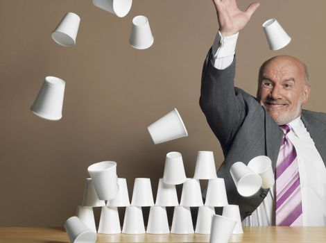 Middle aged businessman knocking down pyramid of plastic cups against brown background