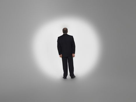 Rear view of a businessman standing in spotlight