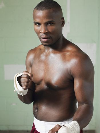 Portrait of a bare chested African American boxer against green wall