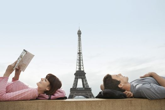 Side view of a couple lying with Eiffel Tower viewed in the background
