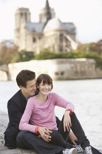 Cheerful couple sitting on riverbank in front of Notre Dame Cathedral