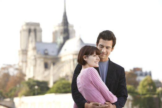 Loving couple standing in front of Notre Dame Cathedral