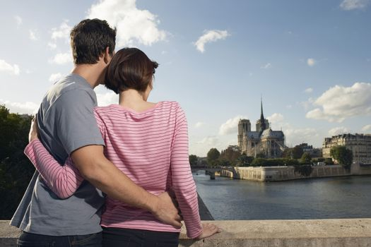 Rear view of a loving couple embracing in front of Notre Dame Cathedral