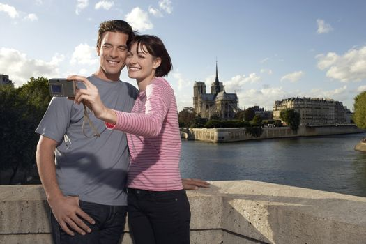 Happy young couple taking photo of themselves in front of Notre Dame Cathedral