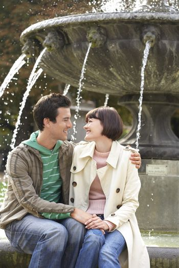 Embracing young couple sitting on edge of fountain