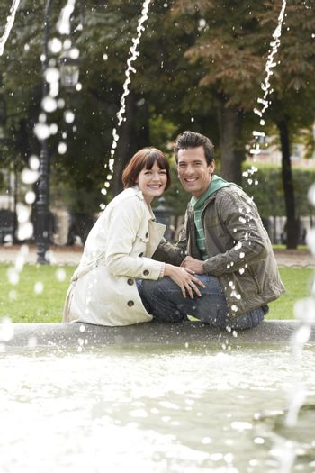 Portrait of a young couple sitting on edge of fountain