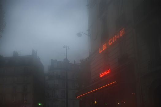 Misty street with buildings against sky at dusk