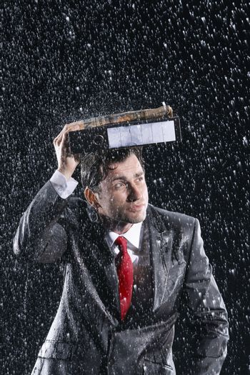 Young businessman covering head with binder in rain