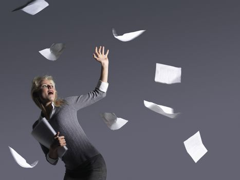Young businesswoman with scattering papers against gray background