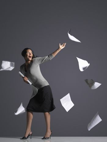 Full length of a young businesswoman with scattering papers against gray background
