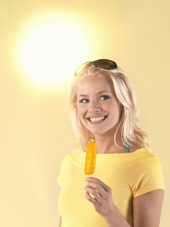 Portrait of a beautiful young woman holding popsicle on a hot summer day