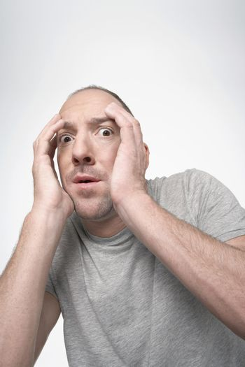 Man hunching down covering face with hands in fear