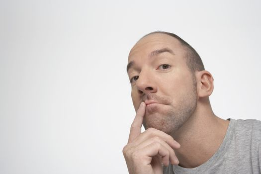 Man with finger on lips thinking