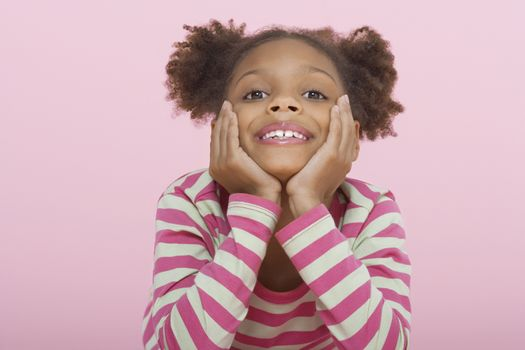 Portrait of a happy girl resting chin in hands on pink background