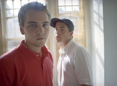 Portrait of young male friends standing in front of window portrait